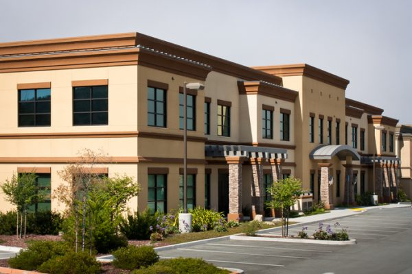 A corner view of a two story office building in an office park with an empty parking lot, in Monterey, California.